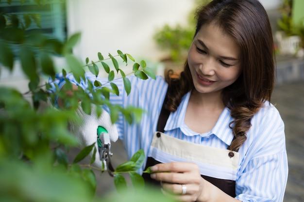 Азиатская милая домохозяйка в фартуке с помощью небольших секаторов подрезает ветви и листья небольшого дерева на заднем дворе дома и счастлива для хобби.