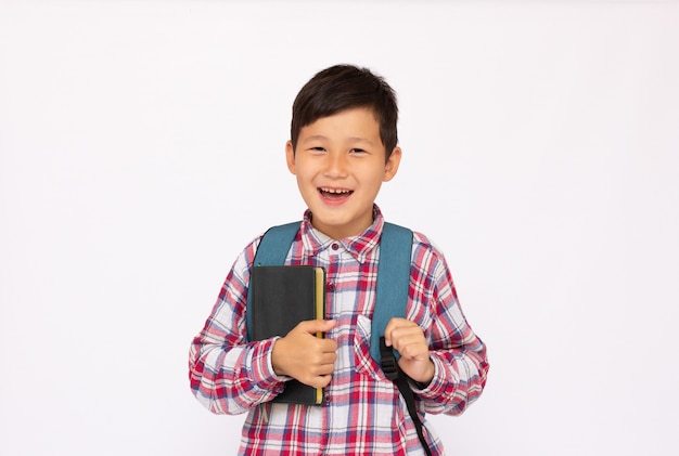 Asian cute kid portrait boy going to school with book and small school bag, isolated over white surface