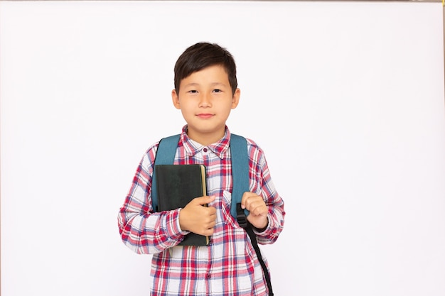 Asian cute kid portrait boy going to school with small school bag, isolated over white surface