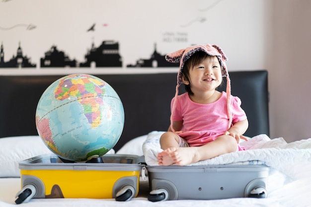 Asian cute little baby girl wearing hat sitting on travel bag with smile feeling funny and laughing on bed in bedroom with world globe put on other side of suitcase bag.