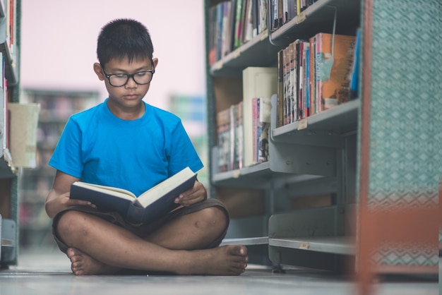 Asian cute little boy reading book in the library