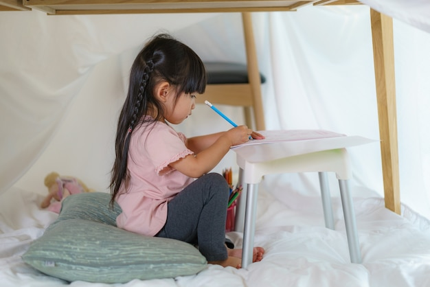 Asian cute little girl drawing in paper while lying in a blanket fort in living room at home