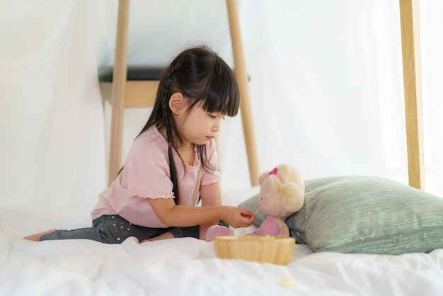 Asian cute little girl play her doll and feeding snack while sitting in a blanket fort in living room at home