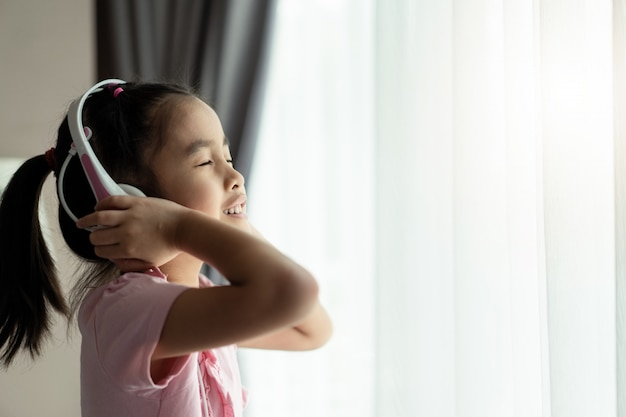 Asian cute little girl using headset listening music in the room.