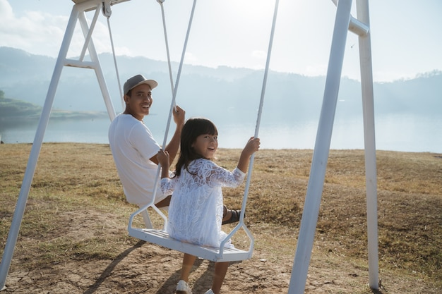 Asian cute little girl with dad enjoys swinging
