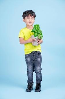 アジアのかわいい小さなハンサムな男の子は、緑の植物と笑顔、環境にやさしいコンセプトの鍋を持っています
