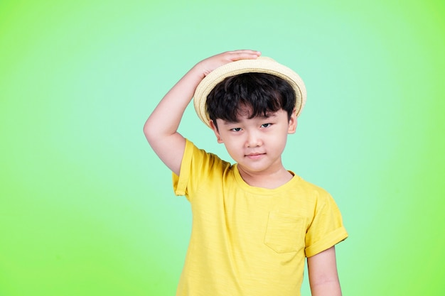 Asian cute little kid boy presenting something with his hand on color background