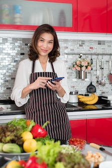 Asian cute middle-age woman in an apron stading using mobile smartphone connect to internet in kitchen with a smiling face and happy manner. concept for modern housewife lifestyle.