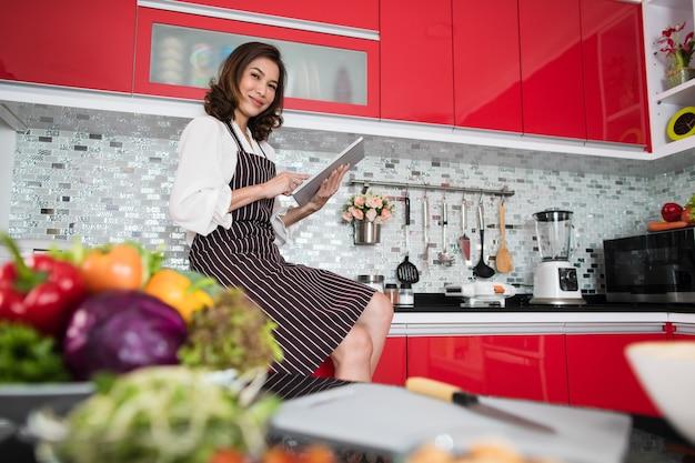タブレットコンピューターを使用してエプロンを着たアジアのかわいい中年女性は、笑顔と幸せな方法でキッチンでインターネットに接続します。現代の主婦のライフスタイルのコンセプト。