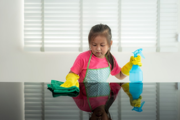 Asian cute preschool student girl washing glass table with green towel in living room at home, with water and detergent solution spray.
