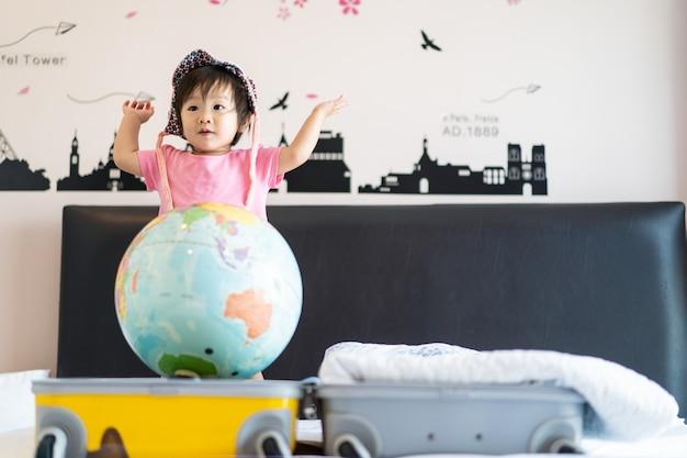 アジアのかわいい笑顔のベッドの上に立って帽子をかぶっている小さな女の赤ちゃんは、面白い感じ、笑って、寝室で踊ります。