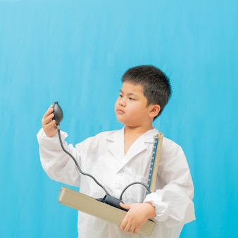 Asian cutea boy holding pressure gauge on blue background,