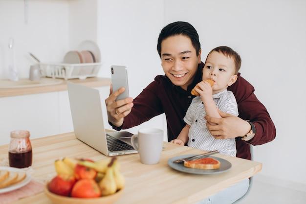 ノートパソコンで朝食をとり、電話でselfieを取るアジアのお父さんと彼の幼い息子