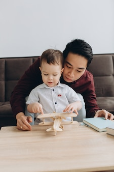 Asian dad and his cute little son playing with a wooden plane in a bright room