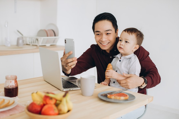 Asian dad and his little son having breakfast at laptop and taking selfie on phone