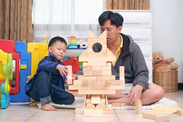 Asian dad and son having fun playing with wooden building block toys at home, happy father and cute little asian  kindergarten boy spending quality time together