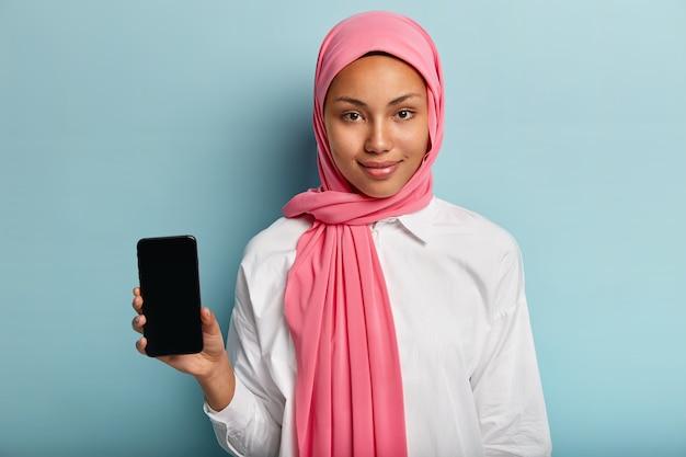 ピンクのスカーフでアジアの暗い肌の女性、白いシャツを着て、青い壁に隔離された画像またはテキスト挿入用のモックアップ画面付きの携帯電話を保持します。セレクティブフォーカス。テクノロジー、文化、広告