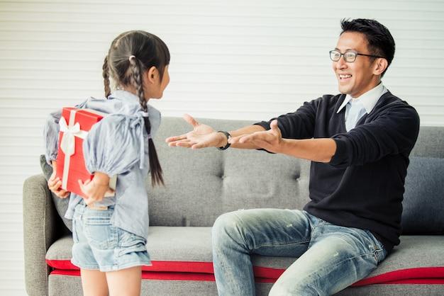 アジアの娘が父親にプレゼントを差し出します。父の日のためのコンセプトサプライズギフトボックス。