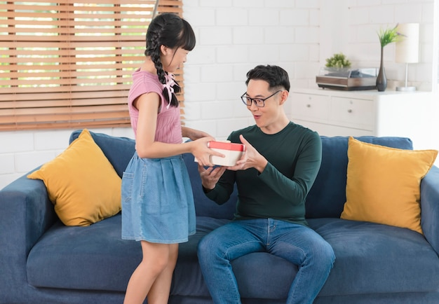 Азиатская дочь дает подарок отцу. концепция сюрприз подарочная коробка на день отцов.
