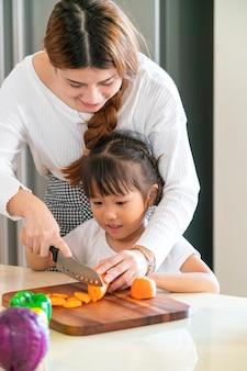 아시아 딸은 그녀의 어머니 절단 당근 저녁 식사, 아시아 가족 개념 요리 음식을 준비하는 데 도움이