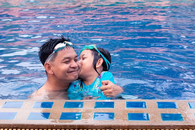 Asian daughter kissing and playing with his father in swimming pool.