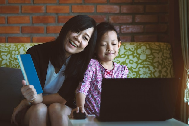 Asian daughter and mother using computer laptop at home with smile and happy.