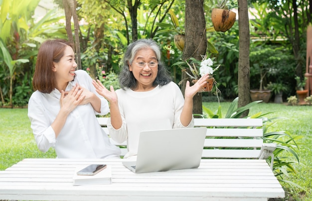 Asian daughter teaching old elderly woman use online social media in computer laptop after retirement.