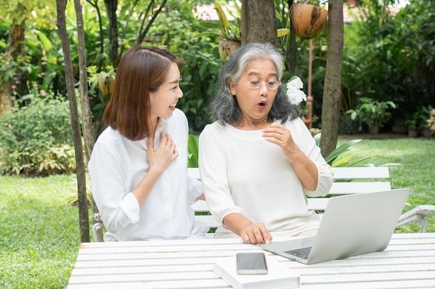 Азиатская дочь учит старуху пожилая женщина использовать онлайн социальные сети в компьютерном ноутбуке