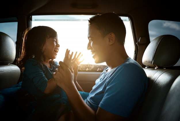 Asian daughter with father in the car playing