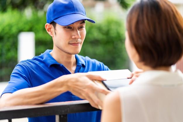 アジア人は家の前でアジア人女性にパッケージボックスを扱う男性を配達します