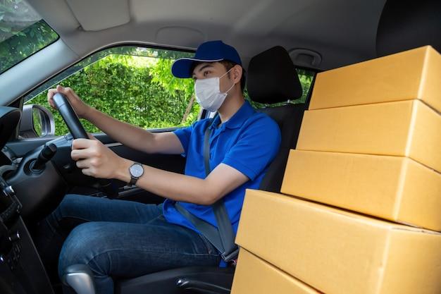 Азиатский курьер работника доставляющего покупки на дом с маской вождения автомобиля поставляя коробки посылки.
