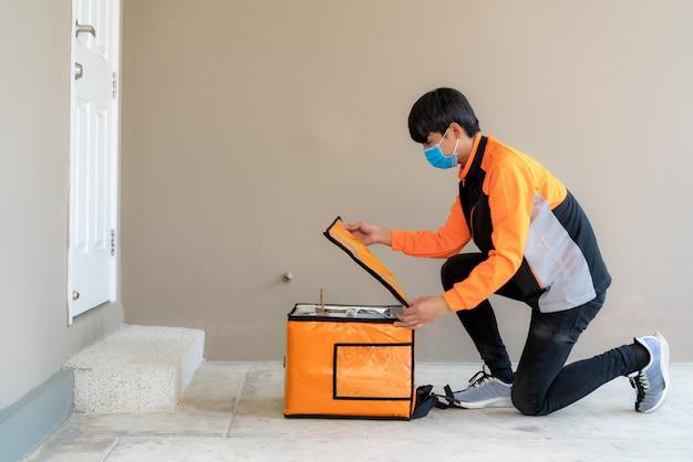 アジアの配達人が感染リスクの社会的距離を保つためにフロントハウスで非接触型または非接触型の配達用フードボックスをドロップして開きます。