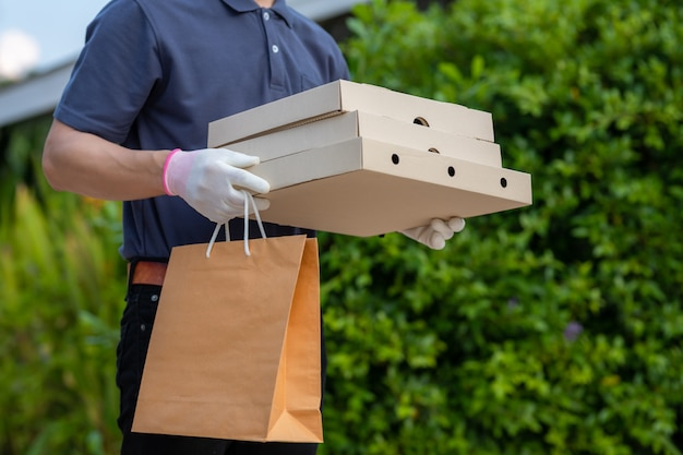 Asian delivery man employee in blue cap t-shirt uniform mask glove hold craft paper packet for takeaway food. concept service quarantine pandemic coronavirus virus [covid-19]