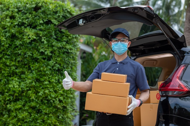 Asian delivery man employee in blue cap t-shirt uniform mask glove hold parcel box. concept service quarantine pandemic coronavirus virus [covid-19]