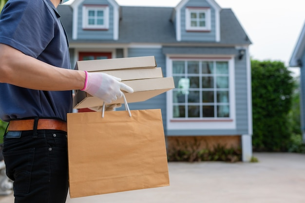 Азиатский работник доставляющий покупки на дом в пакете владением перчатки маски маски футболки голубой крышки бумажном для на вынос еды. концепт-сервис карантинного вируса пандемического коронавируса [covid-19]