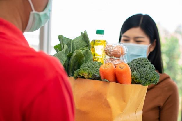 Азиатский работник доставляющий покупки на дом от супермаркета нося лицевой щиток гермошлема и держа сумку свежих продуктов для давать клиентам дома.