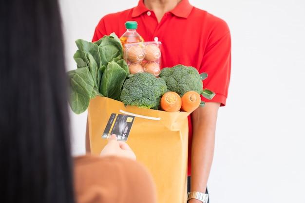 フェイスマスクを着用し、自宅の顧客に与えるために生鮮食品、野菜、果物のバッグを持っているスーパーマーケットからのアジアの配達人。エクスプレス食料品サービスと新しいライフスタイルのコンセプト
