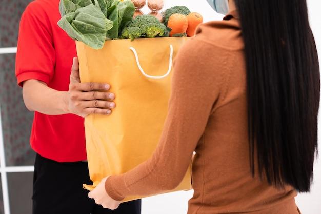 フェイスマスクを着用し、自宅の顧客に与えるために生鮮食品、野菜、果物の袋を持っているスーパーマーケットからのアジアの配達人。エクスプレス食料品サービスと新しいライフスタイルのコンセプト