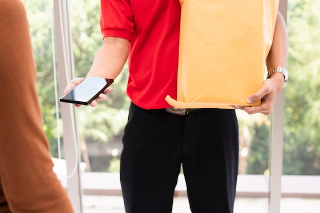 顧客に与えるために生鮮食品の袋を保持し、スマートフォンを保持しているアジアの配達人