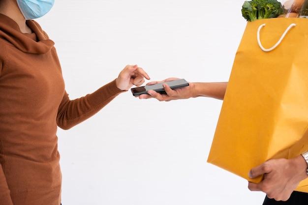 고객에게주고 집에서 지불을 받기 위해 스마트 폰을 들고 신선한 음식 한 봉지를 들고 아시아 배달 남자. 특급 식료품 서비스와 새로운 라이프 스타일의 개념