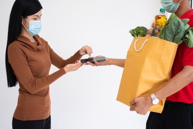 아시아 배달원은 고객에게 줄 신선한 음식 가방을 들고 집에서 지불을 받기 위해 스마트폰을 들고 있습니다. 특급 식료품 서비스와 새로운 라이프스타일의 개념