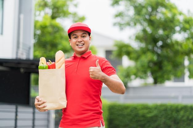 Азиатский доставщик, держащий бумажный пакет с едой