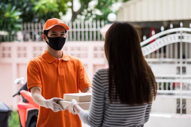 마스크를 쓴 아시아 배달원은 집 밖의 오토바이 근처에서 여성 고객에게 피자 상자를 줍니다. 코로나바이러스 covid-19 델타 팬데믹 기간 동안 집에서 안전하게 배달하세요.