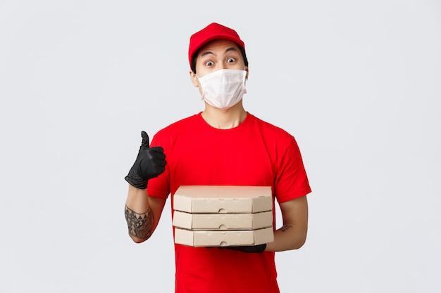 빨간 유니폼, 모자와 티셔츠에 아시아 배달 남자. covid-19 배송시 고객의 안전을위한 보호 장갑, 의료 마스크 착용. 피자 상자를 들고 엄지 위로