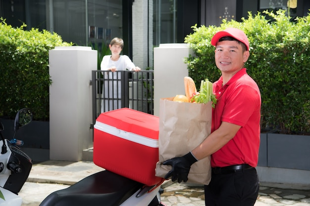 食品、果物、野菜、飲み物の食料品バッグを自宅の女性受信者に配信する赤い制服を着たアジアの配達人