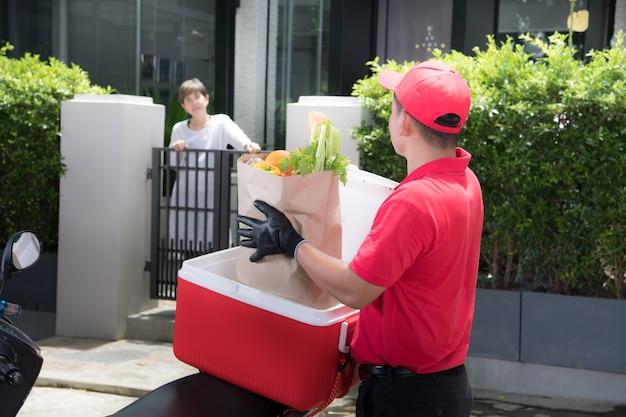 Азиатский курьер в красной форме доставляет коробку с продуктами, фруктами, овощами и напитками женщине-получателю дома