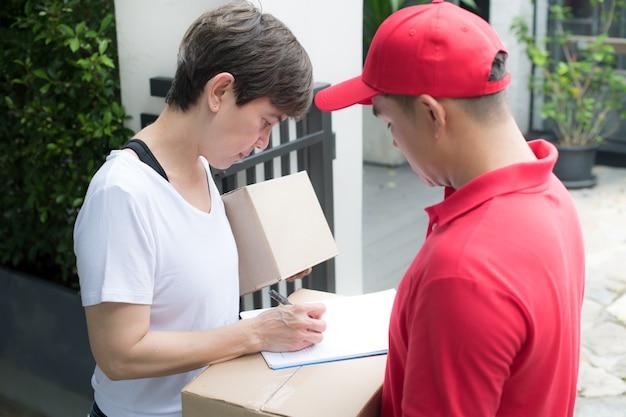 Азиатский курьер в красной форме доставляет посылку женщине-получателю дома