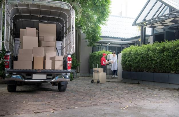 Азиатский курьер в красной форме доставляет посылки женщине-получателю дома