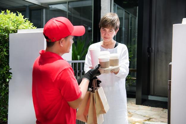 Азиатский курьер в красной форме доставляет пакеты с едой и напитками женщине-получателю дома