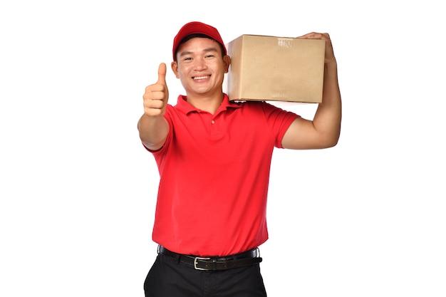 Азиатский курьер в красной форме с картонной коробкой и показывает палец вверх, изолированные на белом фоне